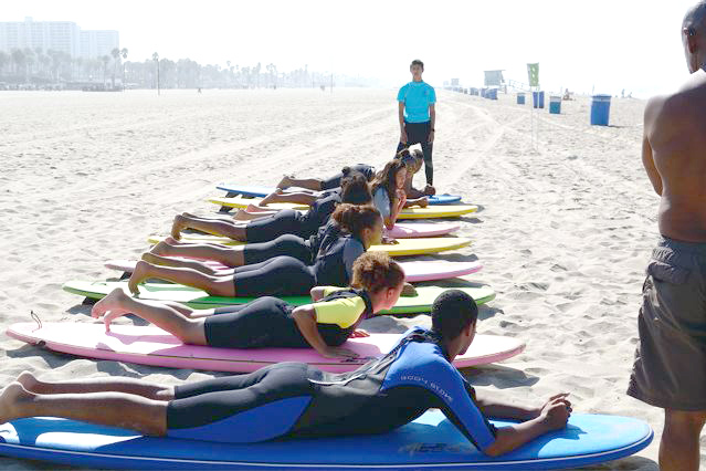 With surf instructors looking on Claremont Colleges' students learn the paddle position and other moves lying on a surfboard to get into position to catch a wave. Claremont University Consortium /Office of Black Student Affairs Incoming Student Retreat, September 15, 2013, Santa Monica, California, photo by Travis Brown. (Click to enlarge)
