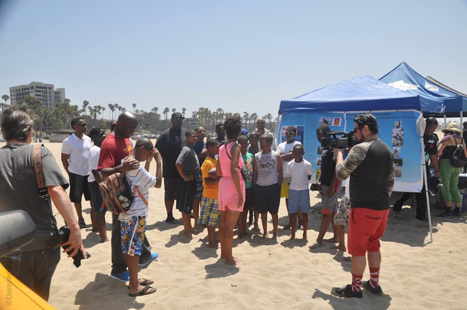 "Youngsters learn about the history of the event site at the Bay Street/Inkwell historic site from historian Alison Rose Jefferson and the banner exhibit entitled, ""Hidden Beach Stories & the California Dream: African Americans, Beach Culture, Santa Monica & the American Narrative"" at Nick Gabaldón Day 2014. Bay Street/Inkwell historic site, Santa Monica, California. Photography by Damien Baskette from the Black Surfers Collective Facebook page. (click to enlarge)"